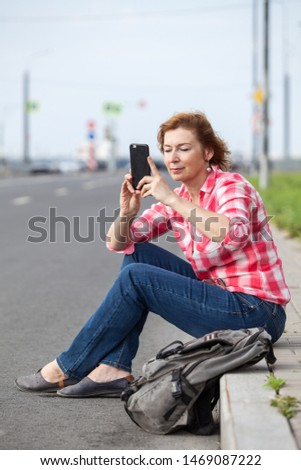 Woman making picture of road with her smartphone, sitting on curb of empty street