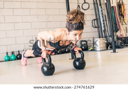 woman making push ups on the kettle bells in a gym. concept about fitness, sport and people