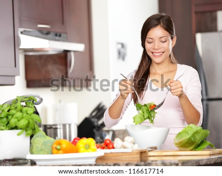 Woman making salad in kitchen. Healthy eating lifestyle concept with beautiful young woman cooking in her kitchen.