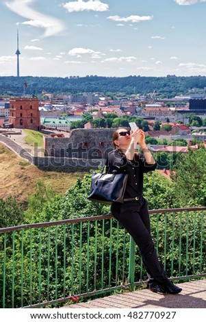 Woman making selfie with Gediminas Tower on the hill and the Lower Castle down the hill in Vilnius in Lithuania. The Tower is also called as Upper Castle. Lithuania is a Baltic country #482770927