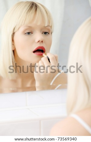 Woman making up her lips at bathroom