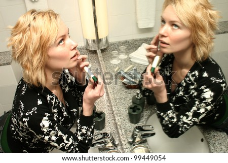 Woman making up her lips near the mirror