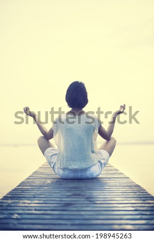 Woman making yoga in a boardwalk