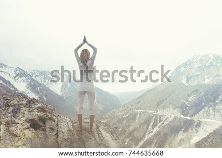 woman making yoga over a mountain