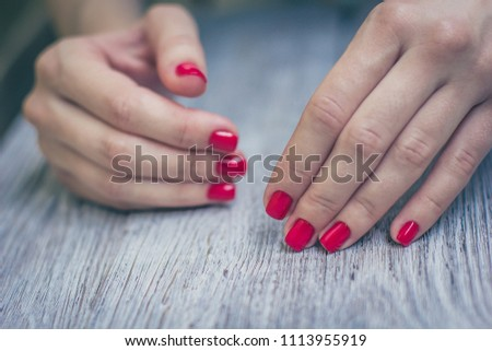 Woman manicured red color nails. Wooden table background