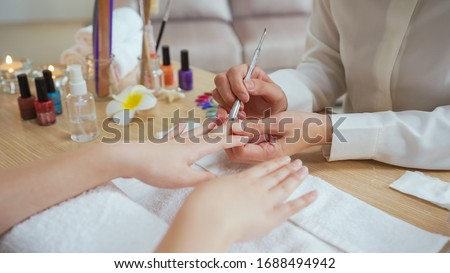 Woman manicurist use nail file drill to cut and fix nail shape of customer in home service beauty treatment. Perfect nails manicure process operation in close up with burst flying debris indoors. Stok fotoğraf ©