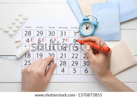 Woman marking her period in menstrual calendar