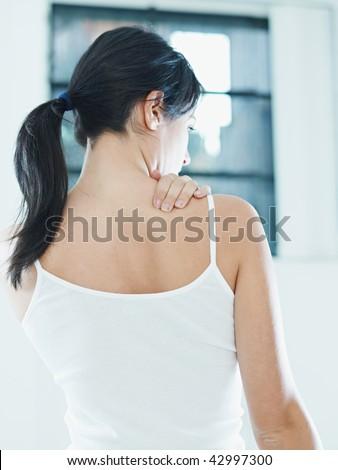 woman massaging neck. Rear view