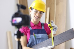 Woman master writes down tips for laying laminate apartments on camera. Selling floor coverings online concept