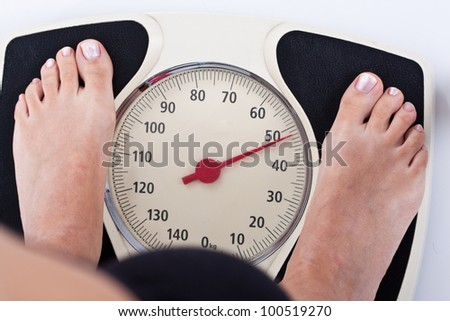 Woman measuring her weight on a balance - stock photo