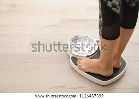 Woman measuring her weight using scales on wooden floor. Healthy diet