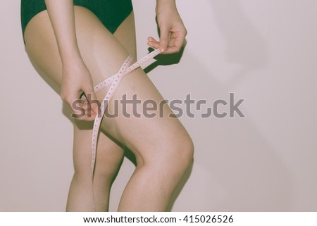 Woman measuring perfect shape of beautiful legs. Healthy lifestyles concept hipster art filter #415026526