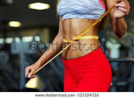 Woman measuring perfect shape of beautiful waist, healthy lifestyles concept #525104326