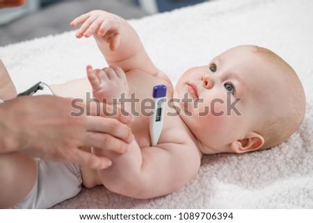Woman measuring temperature of small sick boy