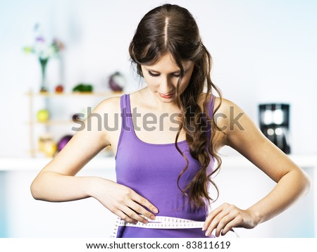 Woman Measuring Waist in kitchen