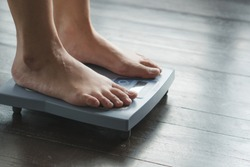 Woman measuring weight on weight scale have a copy space for text.