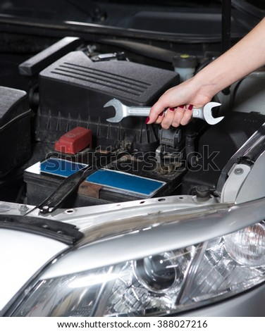 Woman mechanic tuning car with diagnostic equipment. Lady holding wrench to solve problem at service station.