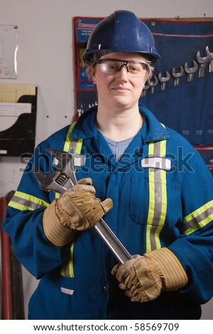 Woman mechanic working in a workshop holding a large wrench wearing protective gloves