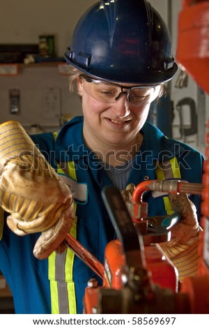 Woman mechanic working in a workshop using a vice grip