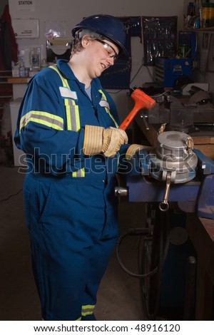 Woman mechanic working in a workshop using a vice grip hammering