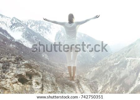 woman meditates on top of the mountain peak