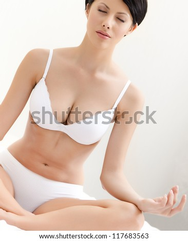 Woman meditates sitting on the bed,