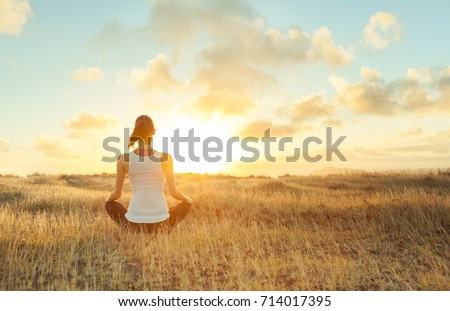 Woman meditating against a beautiful sunset. Mind body spirit.
