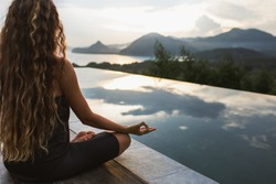 Woman meditating and practicing yoga alone at sunrise near infinity pool with mountains on horizon. Rear view. Travel Lifestyle spiritual relaxation concept. Harmony with nature.