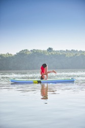Woman meditating and practicing yoga during sunrise in paddle board