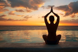 Woman meditating at sunset. Dark female silhouette with raised clasped hands above his head.