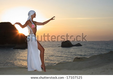 Woman meditating at sunset in Greece