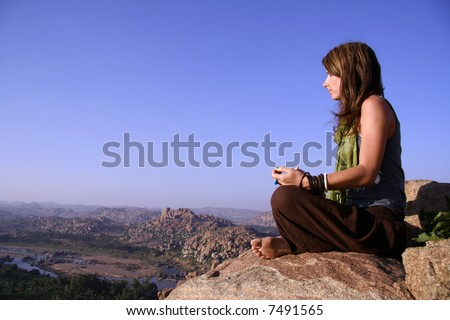 woman meditating at sunset on hilltop in hampi, india