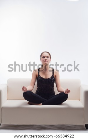 woman meditating in lotus position on the couch