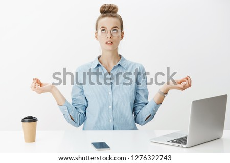 Woman meditating in office sitting near table having break from writing article in laptop, drinking coffee looking up practicing yoga, making nirvana orbs with hands spread aside over gray wall #1276322743
