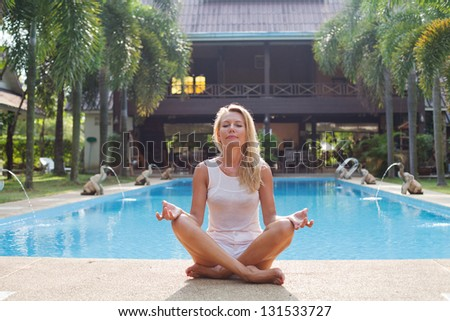 woman meditating near swimming pool