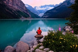 Woman meditating on beach at sunrise. Vacation in Canadian Rockies. Lake Louise in Banff National Park. Alberta. Canada.