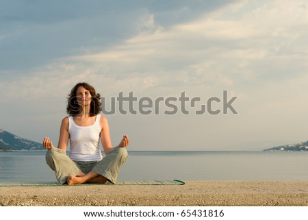 Woman meditating on sea
