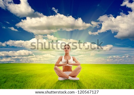woman meditating on summer field over sunset - stock photo