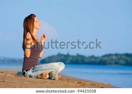 Woman meditating on the river beach.