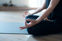 Woman meditating or doing yoga sitting on the mat cold blue tone