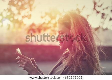 Woman messaging or playing on smartphone vintage style #652171021