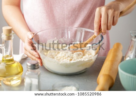Woman mix flour, baking powder, salt, oil and hot water in the glass bowl. Step by step recipe of homemade tortillas. #1085520986