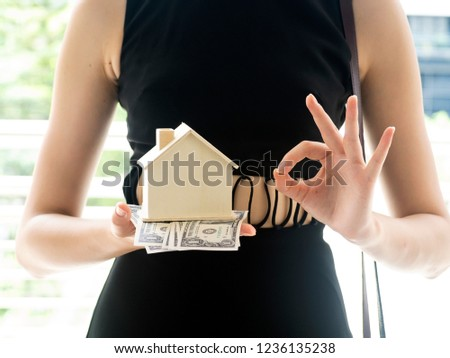 Woman model wearing black dress, holding cash and mini home in her hand. Hand sign meaning O.K., for advertising, investment, home loan, bank agent, residential concept.