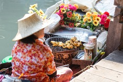 Woman monger is selling grilled squid at Pattaya Floating market