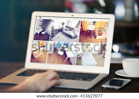 Woman monitoring home security cameras on laptop. Home security system concept