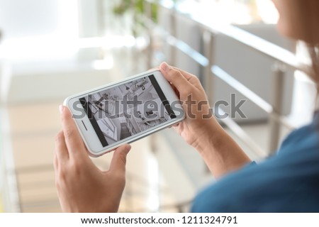 Woman monitoring modern cctv cameras on smartphone indoors, closeup