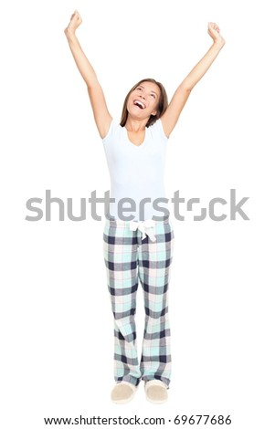 Woman morning stretching in pajamas smiling isolated on white background in full length. Mixed race Asian / Caucasian female model.