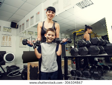 Woman mother with boy and dumbbell in hands in health club. Joint exercise sports with the child. Family mother and son holding different sports dumbbells while standing close to each other in gym.