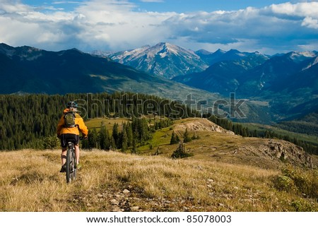 Woman mountain-bike riding on ridge with Ragged Mountains in the distance