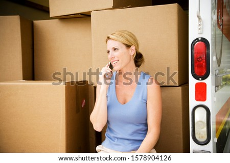 Woman moving home, sitting in the removal van and talking on her mobile phone